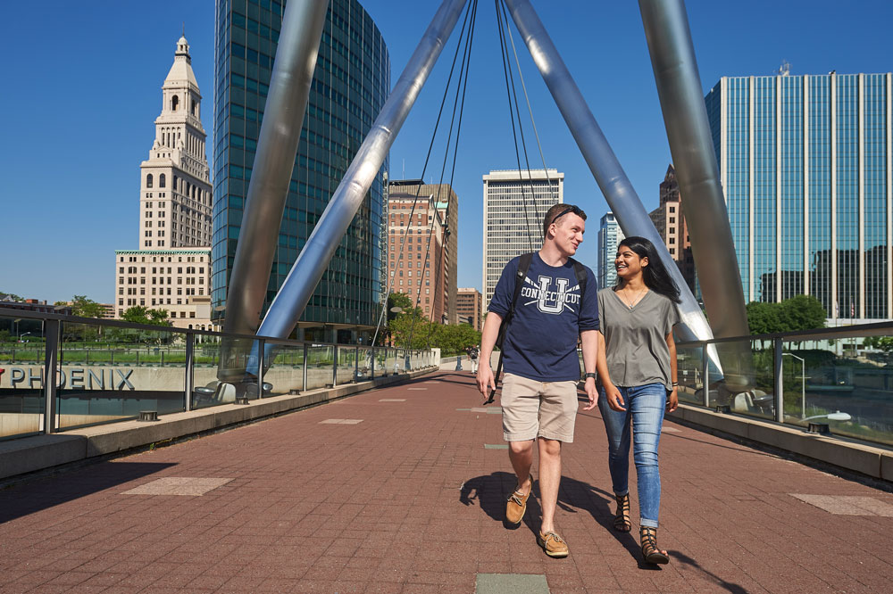 Students walk across the bridge at the Mortensen Riverfront Plaza in Hartford