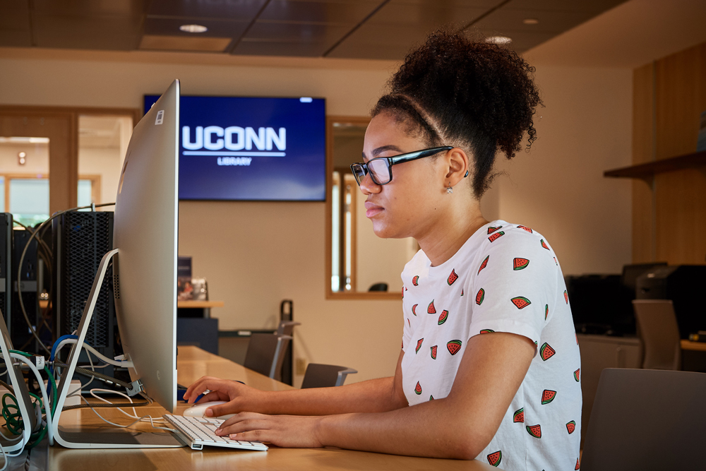 Aubryana Lynch '18 (CLAS) an MSW student, uses a computer at the UConn Hartford Library inside the Hartford Public Library