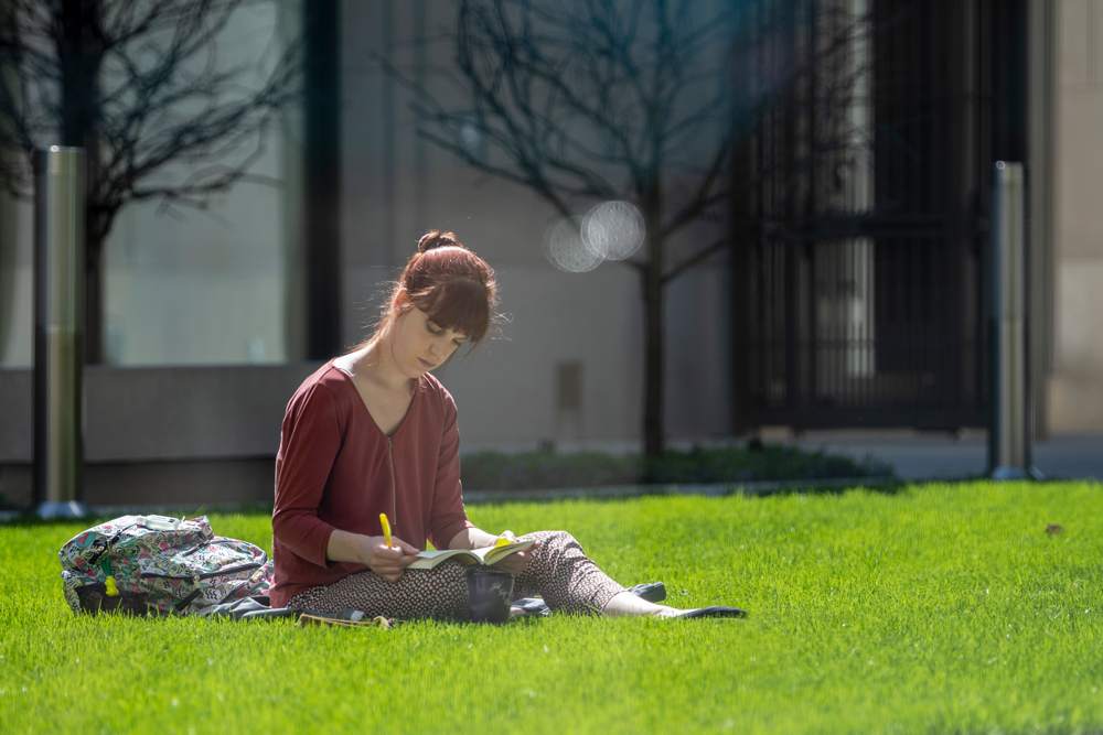 A student reading on the grass of the outdoor courtyard at UConn Hartford